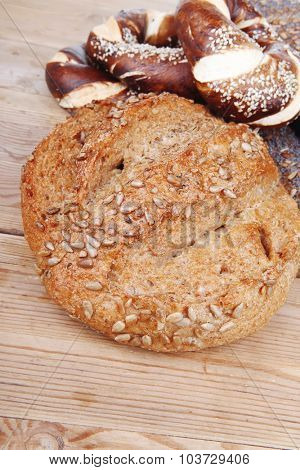 fresh rural homemade rye bread and baguette topped with sunflower seeds and sweet bagels on wooden tables