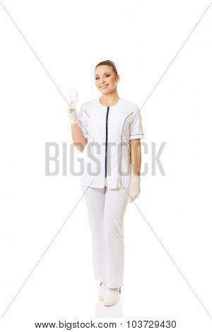 Full length female dentist holding a tooth model.