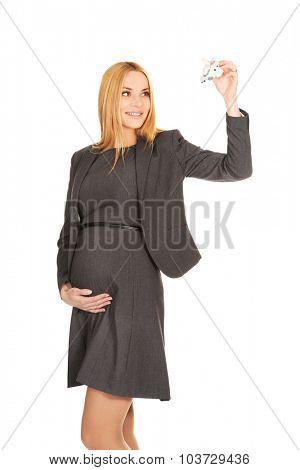 Smiling pregnant businesswoman holding plane model