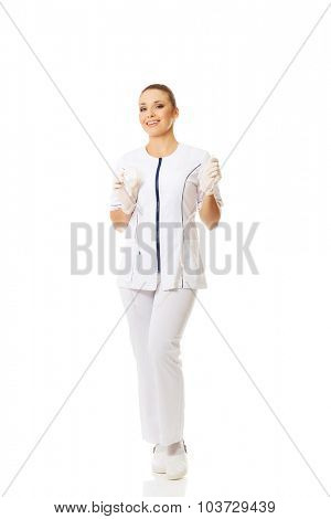 Full length female nurse holding a drip.
