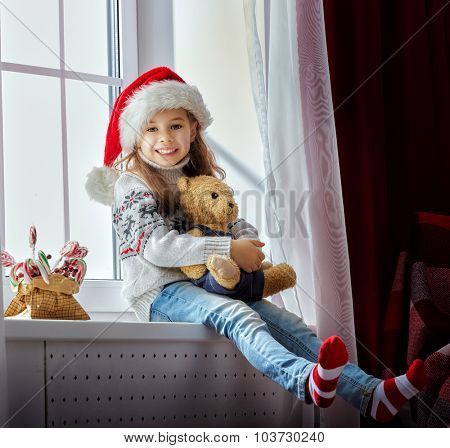 funny girl in Santa hat sitting on the windows