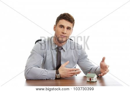 Handsome talking businessman with house model by a desk.
