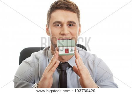 Happy businessman with house model by a desk.