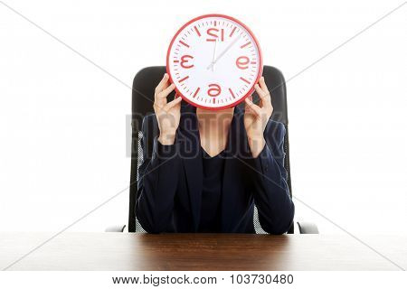 Businesswoman sitting at the desk hiding behind big clock