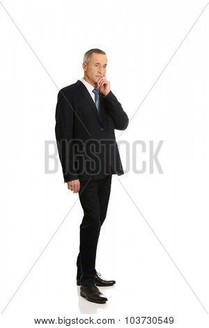 Full length pensive businessman touching chin.