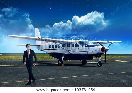 Asian Business Person Walking From Airplane After Landing