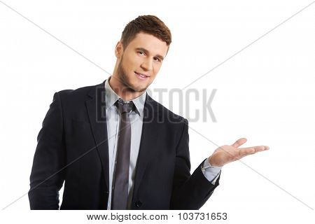 Happy handsome businessman holding copyspace on palm.