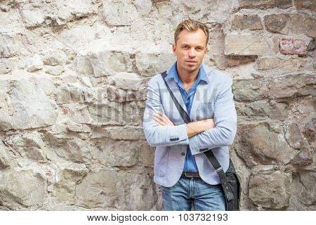 Man standing by the rock wall