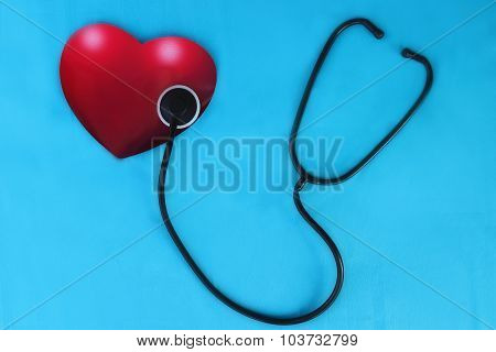 Red heart and a stethoscope on the blue background