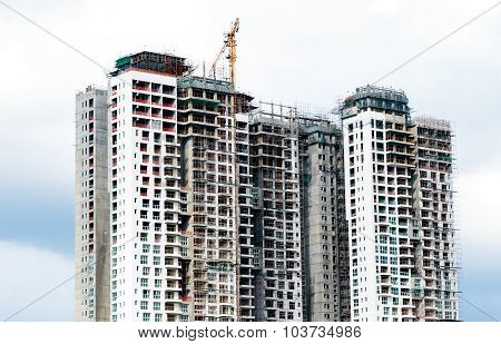 Closeup of a construction site with multistoried apartment on a bright sky background