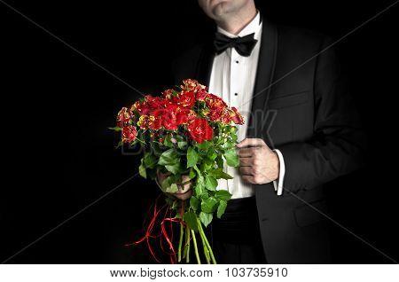 Elegant Man In Tuxedo Holding Red Roses