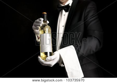 Waiter In Tuxedo Holding A Bottel Of White Wine