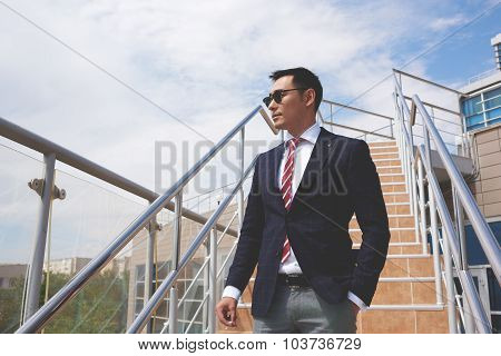 Portrait of a young confident businessman in formal wear resting after hard day