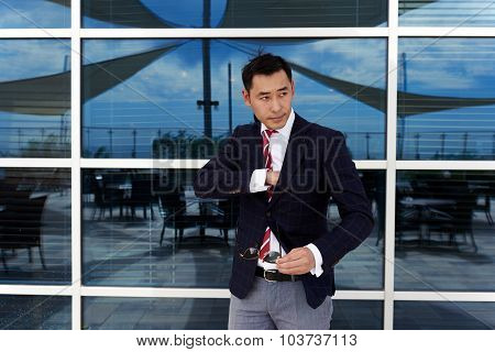 Confident managing director dressed in fashionable luxury clothes posing outdoors in summer day