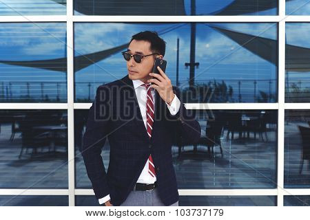Asian businessman dressed in luxury elegant suit talking on his mobile phone
