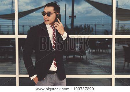 Stylish men entrepreneur talk on mobile phone while standing near office window