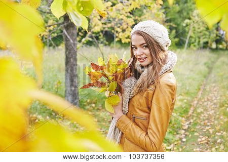 Stylish girl with yellow autumn leaves looking at camera in park