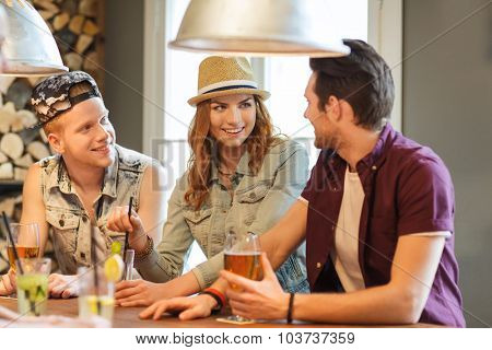 people, leisure, friendship and communication concept - group of happy smiling friends drinking beer and cocktails at bar or pub