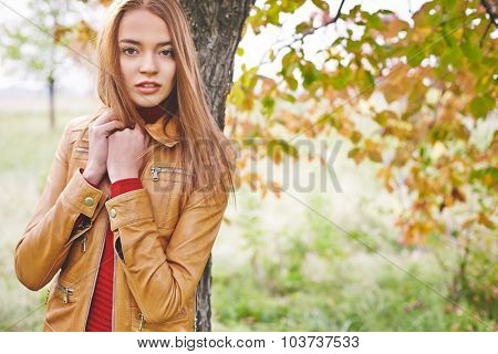 Pretty young woman in leather jacket looking at camera while standing by tree trunk in park