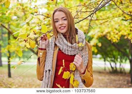 Happy girl in leather jacket, red pullover and knitted scarf looking at camera in park