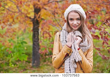 Young female in leather jacket and knitted cap and scarf looking at camera in natural environment