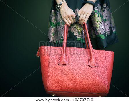 Fashionable beautiful big red handbag on the arm of the girl in a fashionable black dress, posing ne