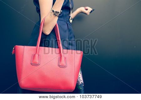 Fashionable beautiful big red handbag on the arm of the girl in a fashionable black dress, posing ne