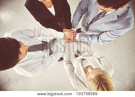 Business team keeping their hands in pile