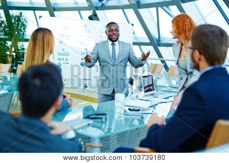 African-american businessman standing by whiteboard and voicing his opinion about data analysis to colleagues
