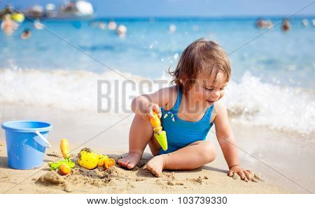 Little girl in blue swimsuit is playing in water