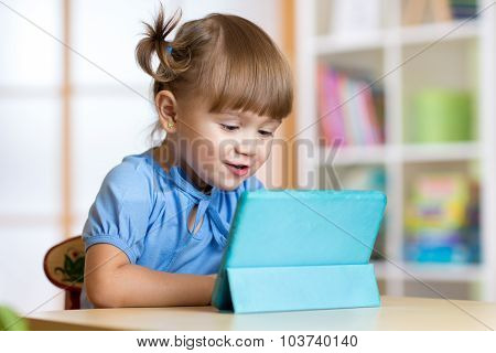 kid girl playing with tablet computer at home