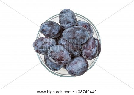 Blue plums in a transparent bowl, top view.