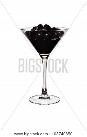 Black olives and juice in a transparent glass close-up