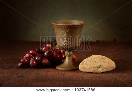 Wine cup surrounded by bread and grapes as symbols of communion