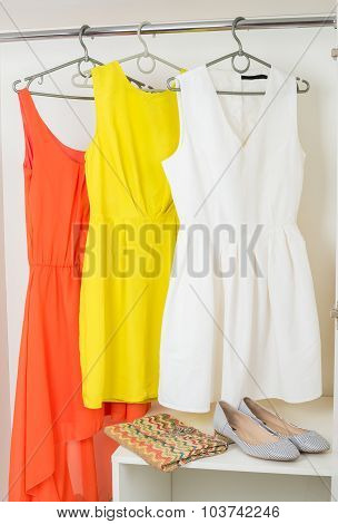 Bright Colorful Dresses Hanging On Coat Hanger, Shoes And Handba