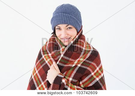 Smiling brunette with checked blanket on white background