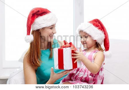christmas, holidays, family, childhood and people concept - happy mother and little girl in santa hats with gift box at home