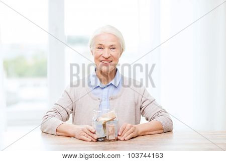 savings, money, annuity insurance, retirement and people concept - smiling senior woman with money in glass jar at home