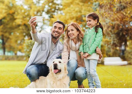 family, pet, season, technology and people concept - happy family with labrador retriever dog taking selfie by smartphone in autumnl park