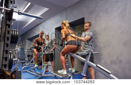 sport, fitness, teamwork and people concept - young woman and personal trainer flexing muscles on gym machine