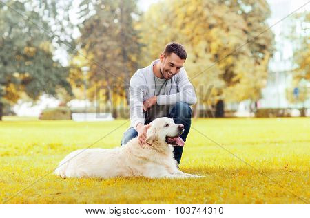 family, pet, domestic animal, season and people concept - happy man with labrador retriever dog walking autumn in city park