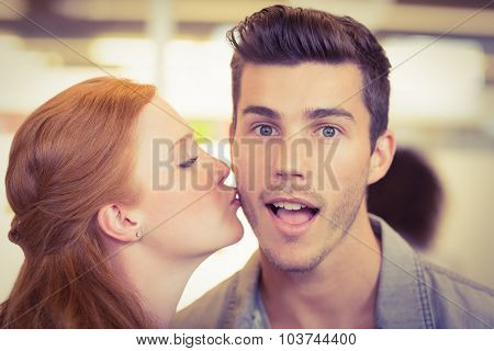 Portrait of shocked businessman being kissed by woman in creative office