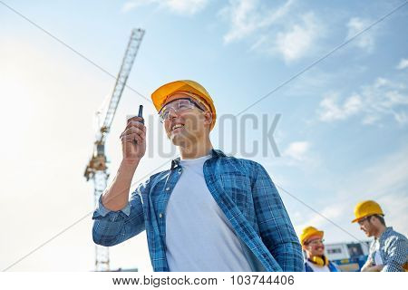 industry, building, technology and people concept -male builder in hardhat with walkie talkie or radio at construction site