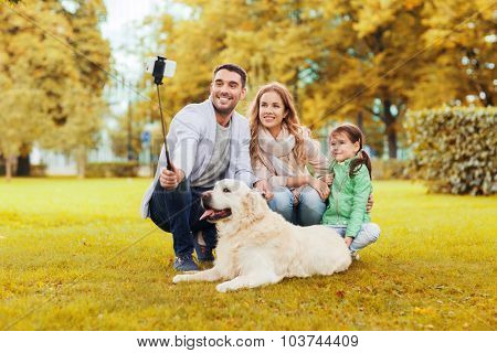 family, pet, season, technology and people concept - happy family with labrador retriever dog taking picture by smartphone on selfie stick in autumnl park