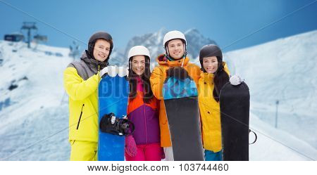 winter, leisure, extreme sport, friendship and people concept - happy friends in helmets with snowboards over downhill skiing and mountains background