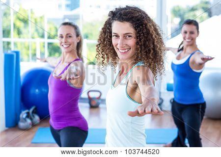 Portrait of fit women doing warrior II pose in fitness studio