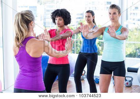 Trainer instructing women at fitness studio