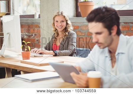 Portrait of young businesswoman working on computer in ooffice