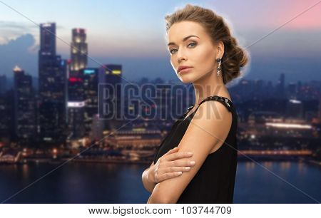 people, holidays, nightlife and glamour concept - beautiful woman wearing earrings over night singapore city background