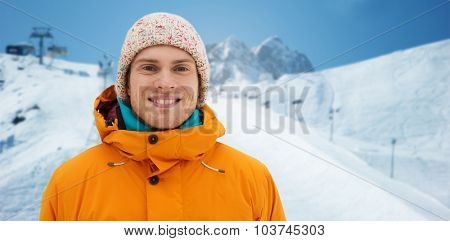 winter, leisure, clothing and people concept - happy teenage boy or young man in winter clothes over downhill skiing and mountains background